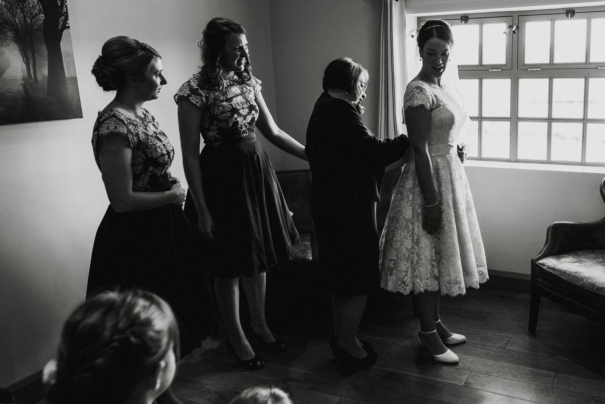 mother of bride fastens wedding dress