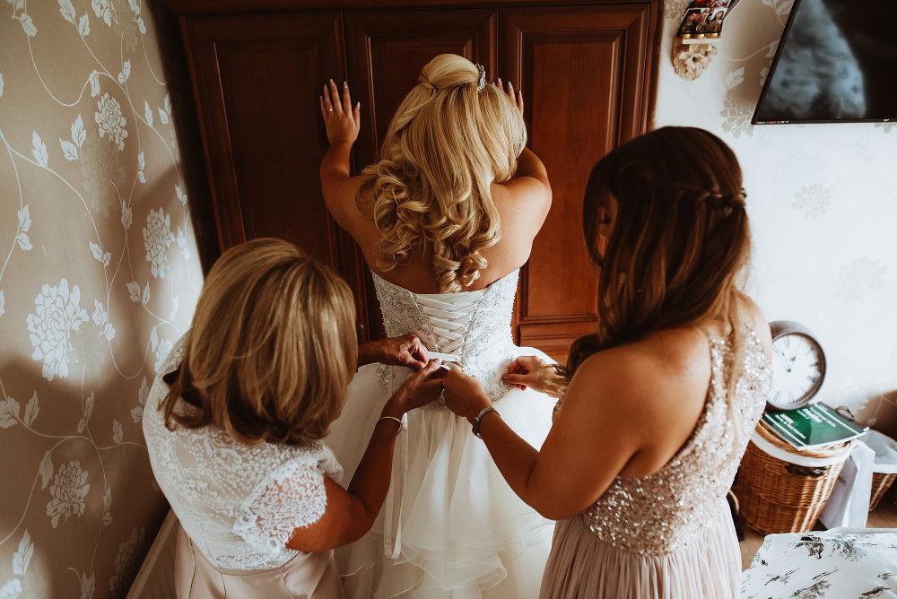 bride gets into wedding dress